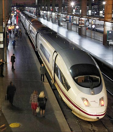 Passengers board the first AVE train linking Madrid to Barcelona at Madrid's Atocha station.