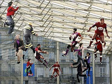 Models of rugby players and citizens hang in the Gare du Nord railway station in Paris.