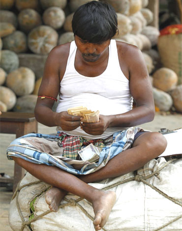A trader counts money at a wholesale vegetable market in Kolkata.