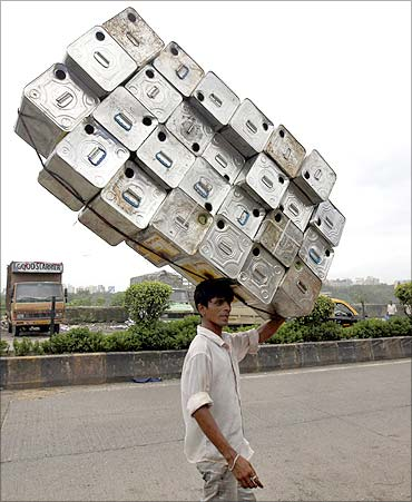 A labourer carries empty tins to a recycling factory in Mumbai.