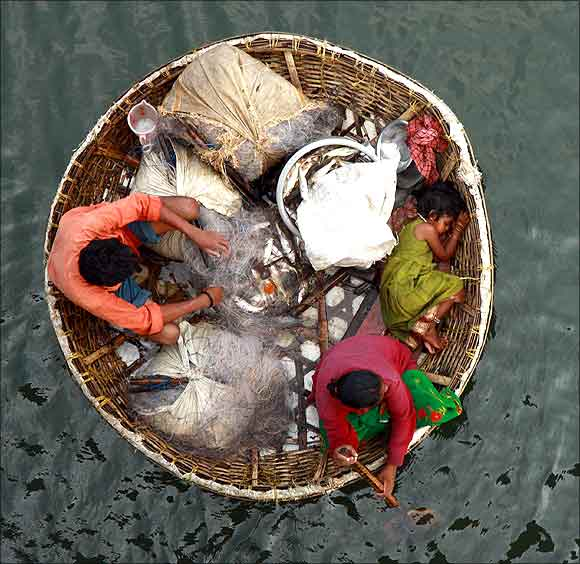 A fisherman arranges a fishing net as his wife paddles their boat in the waters of the Periyar river.