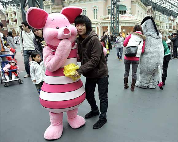A Thai tourist poses with Disney character Piglet at Tokyo Disneyland in Urayasu, north of Tokyo.