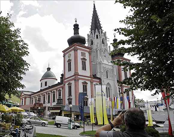 A tourist takes a picture of the basilica of the Styrian town of Mariazell.