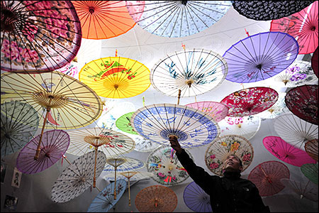A vendor hangs a Chinese paper umbrella onto a string at his stall in an antique market in Xi'an.