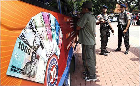 A man collects small rupiah banknotes from a mobile bank van in Jakarta.