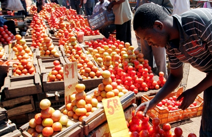 A man buys tomatoes at a vegetable market in Mbare.