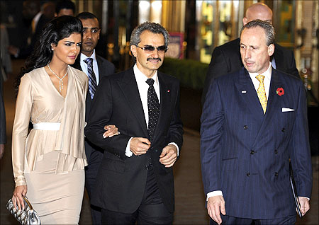 Saudi Prince Alwaleed Bin Talal Bin Abdul Aziz Alsaud (C) walks with his wife Princess Amira (L).
