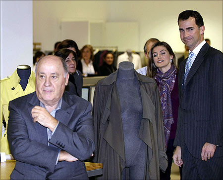 Spain's Princess Letizia and Crown Prince Felipe (R) stand next to chairman of Spanish global fashion group Inditex, Amancio Ortega (L).