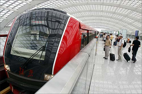 Passengers wait to board the new Airport Express train at the subway station in Beijing.
