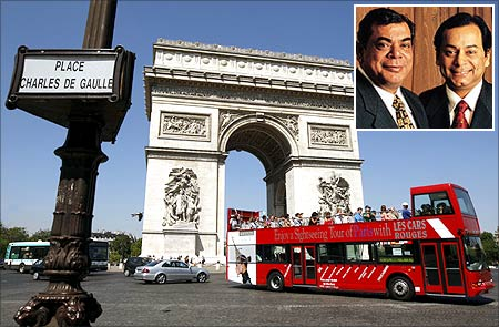 Visitors ride an open-air tourist bus which passes in front of the Arc de Triomphe, near the Champs Elysees in Paris. Shashi and Ravi Ruia (inset).