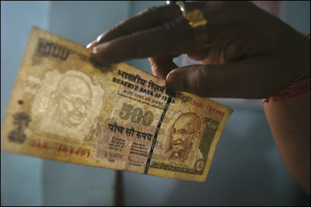 An employee checks a Rs 500 note at a cash counter.