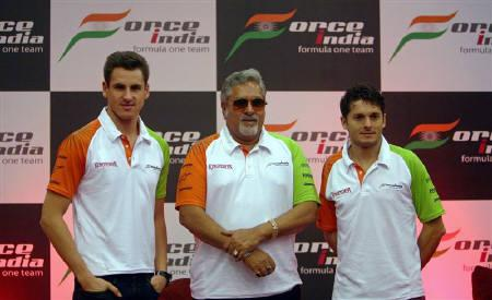 Force India's Formula One team chairman Vijay Mallya (C) poses with drivers Giancarlo Fisichella (R) of Italy and Adrian Sutil of Germany after a news conference in Mumbai March 22, 2009