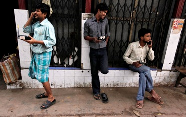 People speak on wireless phones outside the PCO at a wholesale grocery market in Kolkata.