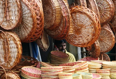 A basket maker speaks on a mobile phone as he waits for customers at a bamboo and cane baskets shop in Hyderabad.