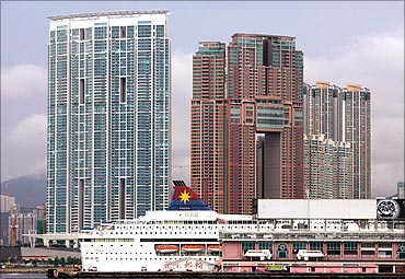 A cruise ship parks in front of two of Hong Kong's most luxurious high-rise residential buildings.