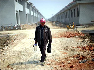 A labourer walks at a construction site.