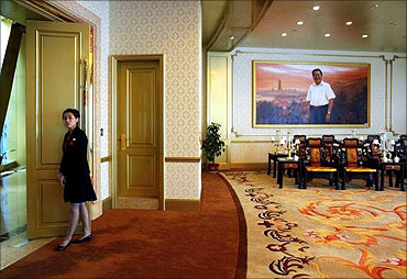 A woman stands at the entrance of a meeting room inside of the new skyscraper tower of Huaxi village.