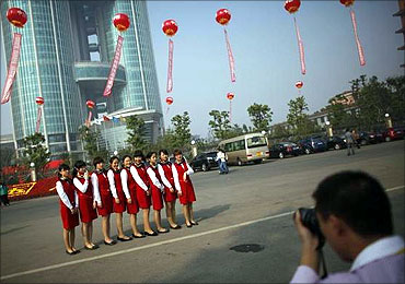 Women pose for a picture in front of the new skyscraper tower of Huaxi village.