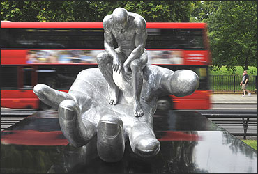 A double-decker bus passes the Hand of God sculpture in central London.