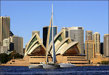 The 34 metre long French-owned trimaran Geronimo crosses in front of the Sydney Opera House.