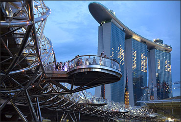 People stand on a platform of the Helix Bridge leading to the Marina Bay Sands casino.