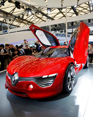 Visitors look at a Renault DeZir car on the opening day of the Shanghai Auto Show.
