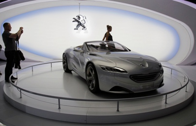 A visitor takes a picture of the Peugeot SR1 Concept car during the Moscow Auto Salon 2010.