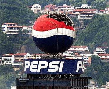 Workers remove panels from a Pepsi ball advertisement in Caracas.