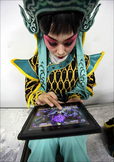 A performer plays a game on an iPad while waiting for a Beijing opera.