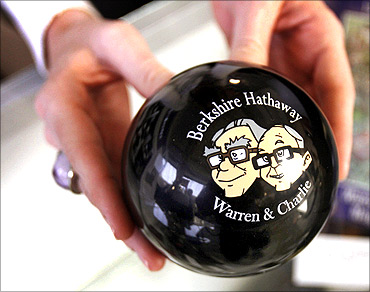 A clerk holds a magic answer ball featuring images of Berkshire Hathaway Chairman Warren Buffett (L) and Vice-Chairman Charlie Munger.
