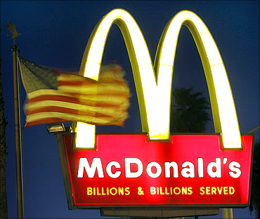 A US flags flutters in the wind in front of a sign for a McDonald's restaurant in Los Angeles.