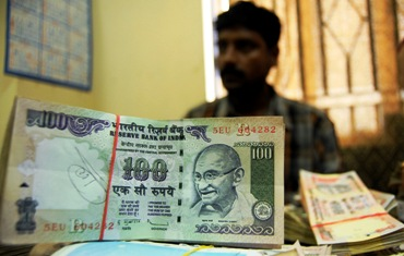 An employee arranges Indian currency notes at a cash counter inside a bank in Agartala.