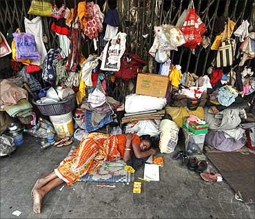 A woman sleeps in front of her belongings, hanging from the shutters of a shop, in Kolkata.