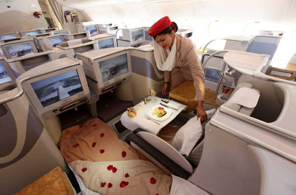 A stewardess adjusts a pillow in the business-class section of an Emirates Airbus A380 at the ILA Berlin Air Show, Germany.