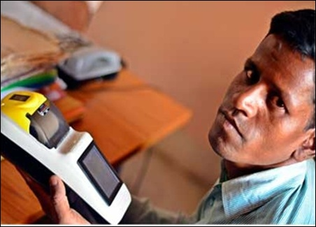 Rajesh Kumar, a former science teacher and currently the banking correspondent of Ramgarh's Dohakatu village, shows off his Micro ATM, which is used to make Aadhaar-enabled MNREGA payments.