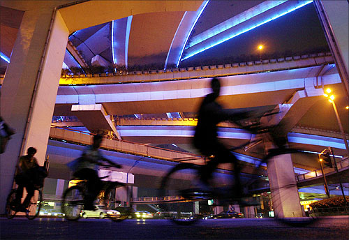 Cyclists pedal under the colourful Yanan elevated highway in Shanghai.