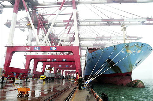 Employees unload containers from a cargo ship as frontier inspection soldiers (C) stand guard at Qingdao port during a rainy day in Qingdao, Shandong province.