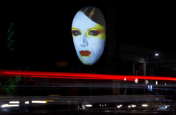 Cars travel past the 'Faces of Berlin' light installation during the Festival of Lights in Berlin.