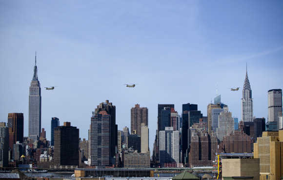 Three US Army CH-47 Chinook helicopters with 10th Combat Aviation Brigade's 6-6 Cavalry fly past skyline of New York.