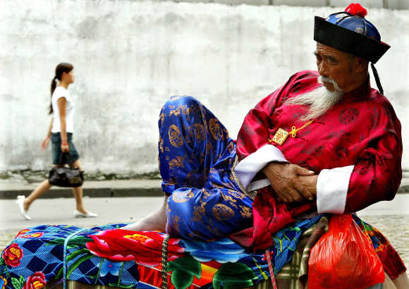 A Chinese man wearing a colourful traditional attire dozes near a tourist shopping district in Shanghai.