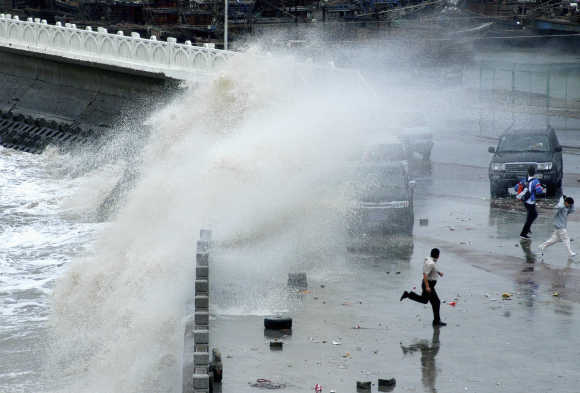 People run away from big waves affected by Typhoon Krosa at a levee in Lianyungang, China.