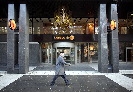 A man walks past the Swedbank head office in Stockholm.