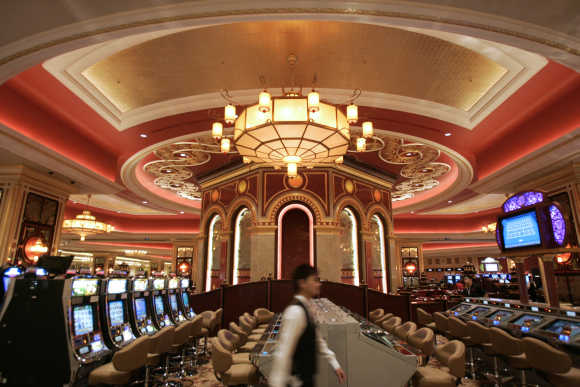 An employee walks past the slot machines in the casino at the Venetian in Macau.