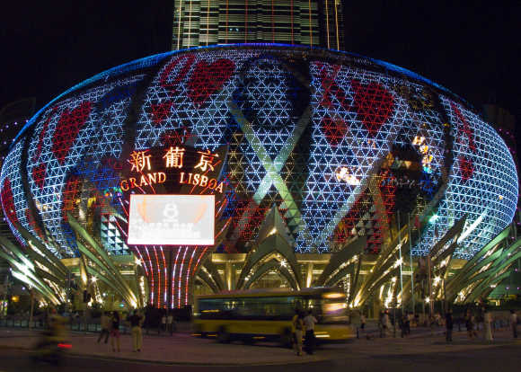 People walk past the Grand Lisboa Casino in Macau.