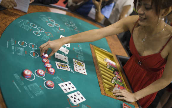 A female croupier places casino chips during the Global Gaming Expo Asia in Macau.