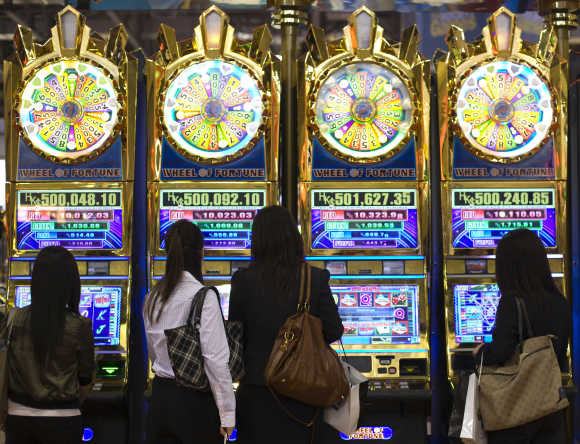 Women play slot machines during the Global Gaming Expo Asia at the Venetian Macao-Resort-Hotel in Macau.