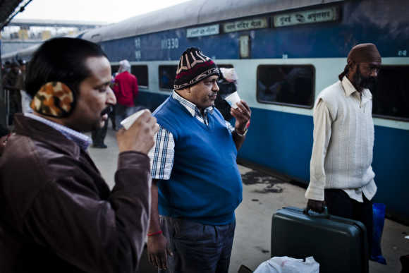 Men drink tea on the platform prior to departing from the Nizamuddin Railway Station in New Delhi.