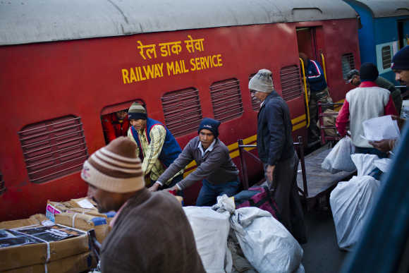 Workers load mail onto a train at Nizamuddin Railway Station.