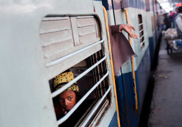 A girl peers out from a carriage at Nizamuddin Railway Station.