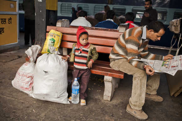 A boy waits with his family belongings prior to boarding a train at the Nizamuddin Railway Station.